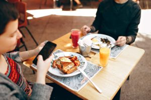 People using mobile devices while eating- utilizing customer feedback is a great restaurant marketing idea.