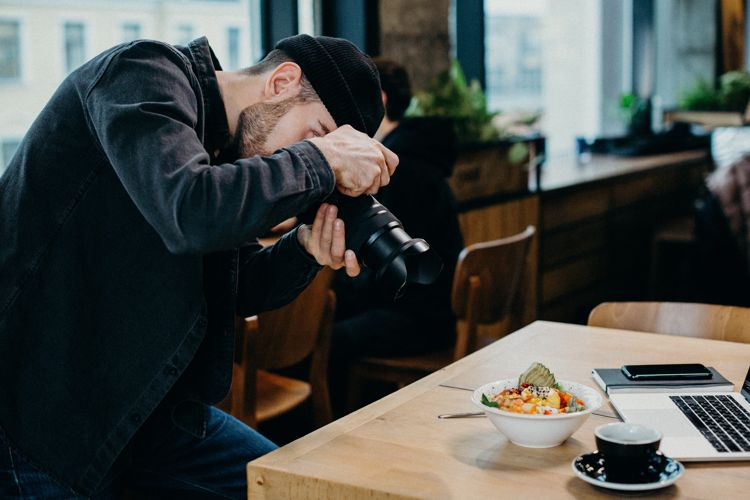 Man taking photo for restaurant marketing.